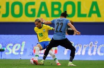 Antony (i) de Brasil disputa el balón con Martín Cáceres de Uruguay. EFE