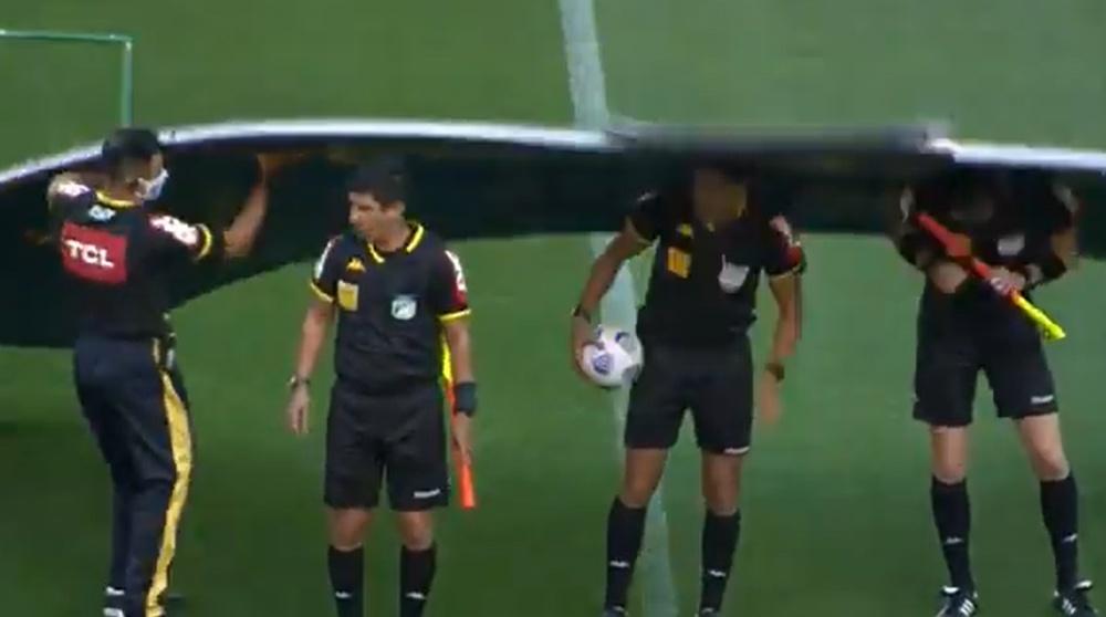 Los árbitros posaron para la foto... ¡y les cayó encima la cartelería! Twitter/BrasileiraoPlay